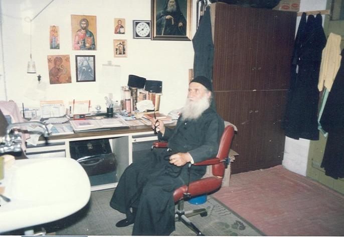Εδώ ο Γέροντας μπροστά στο γραφείο του, όπου περνούσε πολλές ώρες απαντώντας στα πολλά γράμματα που του έστελλαν και συγγράφοντας τα βιβλία που μας άφησε ως παρακαταθήκη.