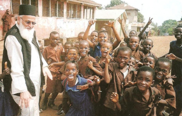 Ο π. Θεμιστοκλής  με τα παιδιά στο προαύλιο του σχολείου.