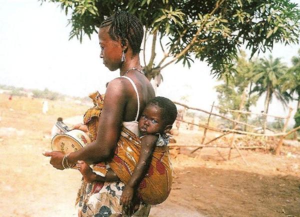 Νεαρή μητέρα η οποία συνδυάζει παρ΄ όλη την φτώχειά της, την παράδοση -μεταφέρει το παιδί της στην πλάτη της- και την τεχνολογία -κρατόντας το κινητό στο χέρι-.