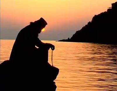 monk praying sunsetη...