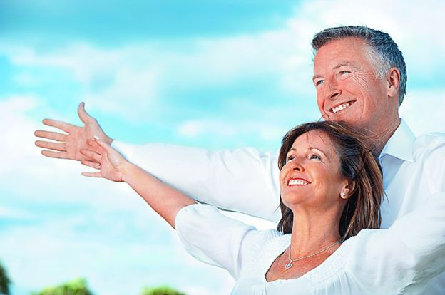 Mature couple holding out their arms